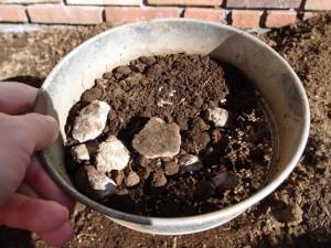 土ふるいを使って石を取り除く