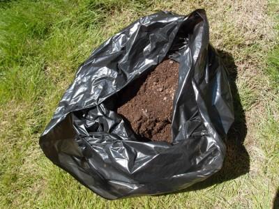 黒いポリ袋に土を入れる